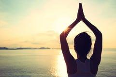 Yogakvinnameditation på soluppgångsjösidan Royaltyfri Bild
