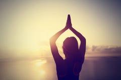 Yogakvinnameditation på soluppgångsjösidan Arkivfoto