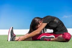 Yogakvinnan som sträcker ett ben böjer framåtriktat, elasticitet Arkivbilder