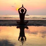 Yogakvinnasammanträde i lotusblomma poserar på stranden Arkivbilder