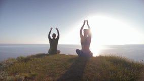 Yogalebensstil, junger Mann und Frau im Sonnenlicht, die auf den Berg betrachtet das Meer meditiert in Lotussitz sitzt stock video footage