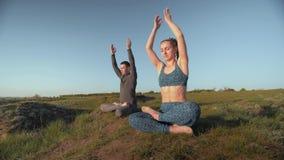 Yogalebensstil, zur Schau tragende Frau und Mann auf Wiese zusammen meditierend in Lotussitz auf Hintergrund des Himmels stock video footage