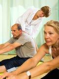 Yogalehrer, der asana zu den reifen Paaren zeigt Stockfotografie