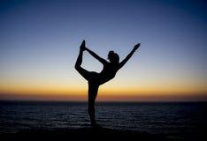 Yogaleraar het stellen bij zonsondergang in een silhouet achtergrond stock fotografie