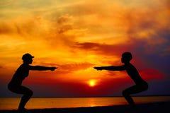 Yogaleute, die draußen in der Kriegershaltung durch Strand bei Sonnenaufgang oder Sonnenuntergang ausbilden und meditieren lizenzfreies stockbild
