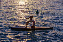 Yogamädchen über SUP stehen oben Brandungsbrett Stockbilder