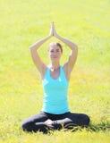 Yogamädchen meditiert, sitzend auf Gras am Sommertag lizenzfreie stockfotos