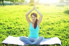 Yogamädchen meditiert, sitzend auf Grashaltungslotos im Sommer lizenzfreies stockfoto