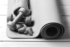 Yogamat Het vormen en geschiktheidsmateriaal Barbells dichtbij cyaan metend bandbroodje Stock Foto's