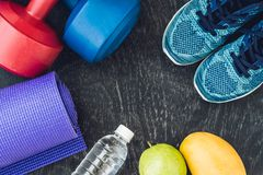 Yogamat, sportschoenen, domoren en fles water op blauwe achtergrond Concepten gezonde levensstijl, sport en dieet De sport equipm Stock Foto