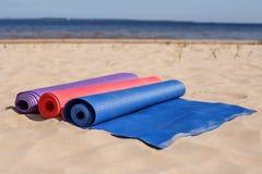 Yogamats som kastas på stranden - förbereda sig för kursen arkivbild