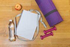Yogamatte, -Notizblock, -apfel, -Dummköpfe und -flasche Wasser Lizenzfreie Stockfotografie