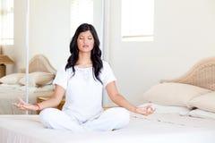 Yogameditation auf Bett Stockfotografie