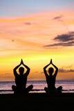 Yogameditation - konturer av folk på solnedgången Royaltyfria Bilder