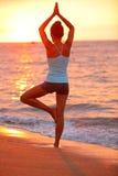 Yogameditationsfrau, die bei Strandsonnenuntergang meditiert Lizenzfreie Stockfotografie