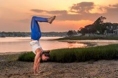 Yogamodell Doing en handstans på stranden på solnedgången Royaltyfria Bilder