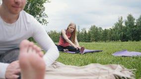 Yogaoefeningen in park - de jonge sportmannen voert flexibiliteit opleiding uit openlucht stock videobeelden