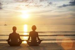 Yogapar som mediterar på kusten under den fantastiska solnedgången Royaltyfri Foto