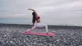 Yogapraxis auf einem Strand morgens stock video footage