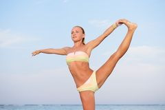 Yogapraxis. Dünne Frau, die durch das Meer übt Stockfotografie