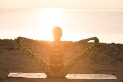 Yogapraxis. Frau, die Yogahaltung am Sonnenaufgang tut Stockfotos