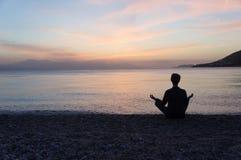Yogaschattenbild auf dem Strand bei Sonnenuntergang Lizenzfreies Stockfoto