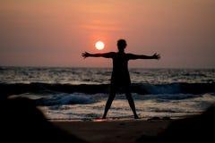 Yogaschattenbild bei Ozeankosten und Sonnenuntergang Indien Stockfotografie