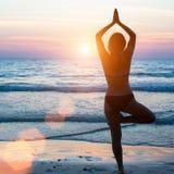 Yogaschattenbildfrau, die Meditation nahe dem Ozeanstrand tut liebhaberei Lizenzfreie Stockbilder