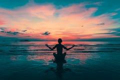 Yogasilhouet Meditatiemeisje op het overzees tijdens verbazende zonsondergang royalty-vrije stock foto's