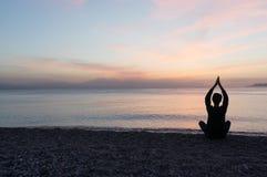 Yogasilhouet op het strand bij zonsondergang Stock Foto