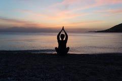 Yogasilhouet op het strand bij zonsondergang Royalty-vrije Stock Foto