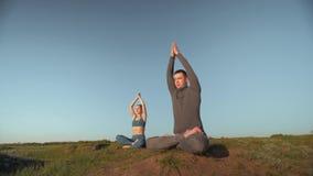 Yogatherapie, athletische Frau und Mann, die zusammen in Lotussitz auf Bergspitze auf Hintergrund des blauen Himmels meditiert stock video footage