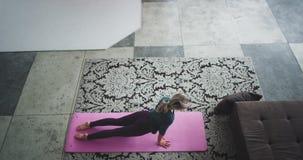 Yogatiddamen som hemma sträcker kroppen i morgonen i hennes stads- vind som uppifrån fångar videoen, gör hon stock video