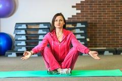 Yogautbildning Den härliga vita flickan i en rosa sportdräkt mediterar på yogagruppen på konditionmitten arkivbilder