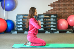 Yogautbildning Den härliga vita flickan i en rosa sportdräkt mediterar på yogagruppen på konditionmitten royaltyfri bild