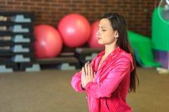 Yogautbildning Den härliga vita flickan i en rosa sportdräkt mediterar på yogagruppen på konditionmitten arkivfoto