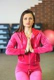 Yogautbildning Den härliga vita flickan i en rosa sportdräkt mediterar på yogagruppen på konditionmitten royaltyfria foton