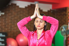 Yogautbildning Den härliga vita flickan i en rosa sportdräkt mediterar på yogagruppen på konditionmitten royaltyfria bilder