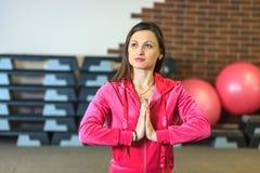 Yogautbildning Den härliga vita flickan i en rosa sportdräkt mediterar på yogagruppen på konditionmitten arkivbild