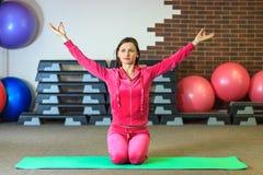 Yogautbildning Den härliga vita flickan i en rosa sportdräkt mediterar på yogagruppen på konditionmitten arkivfoton