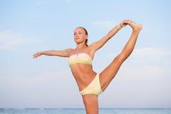 Yogaövning. Slank kvinna som öva vid havet Arkivbild