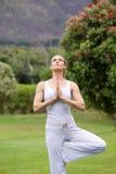 Yogavrouw die buiten in park uitoefenen Stock Afbeeldingen