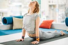 Yogavrouw die uitrekkende oefening op de vloer doen royalty-vrije stock foto
