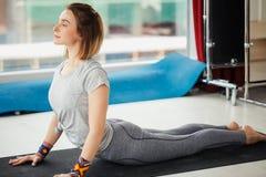 Yogavrouw die uitrekkende oefening op de vloer doen royalty-vrije stock afbeeldingen