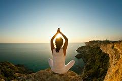 Yogavrouw die yoga op achtergrond van aard en overzees doen Stock Fotografie