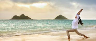 Yogavrouw het mediteren in strijder die ik bij strand heb gesteld stock fotografie