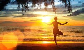 Yogavrouw op overzeese kust bij zonsondergang meditatie Stock Foto's