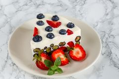 Yoghurt cake with berries. On a dish with strawberries and mint royalty free stock photography