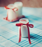 Yoghurt, cream, sour  in a glass jar with  tape  polka dots on  napkin, towel. Yoghurt, cream, sour cream in a glass jar with a tape with polka dots on a napkin Royalty Free Stock Image
