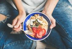 Yoghurt, granola, frö, nya torra frukter och honung i bunke royaltyfri fotografi